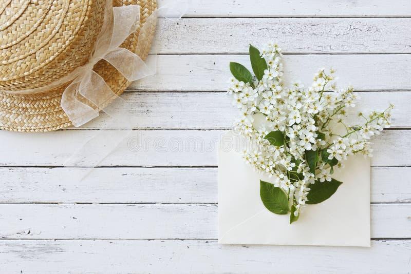 Foto del primo piano del cappello vicino alla busta con i bei rami di albero di fioritura su fondo di legno bianco immagine stock libera da diritti
