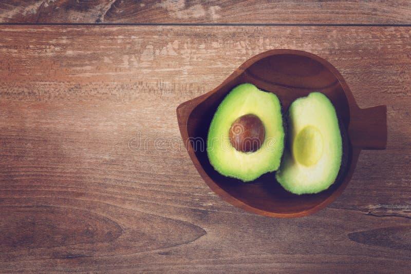 Foto del primo piano degli avocado affettati freschi in ciotola marrone su fondo di legno marrone Vista superiore Copi lo spazio fotografia stock