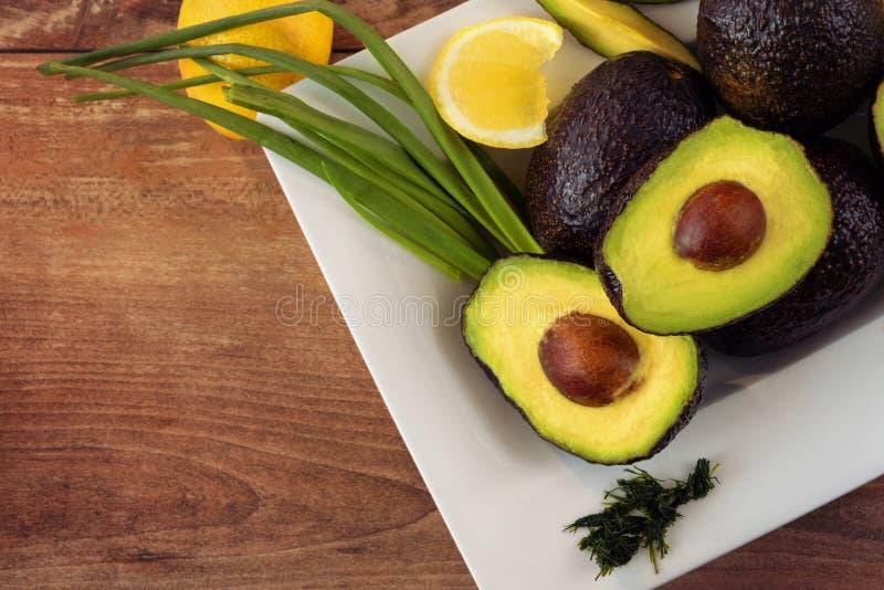 Foto del primo piano degli avocado affettati freschi, della cipolla fresca e dei pezzi di limone nel piatto di porcellana bianco  fotografia stock