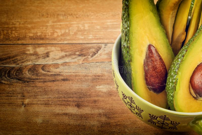 Foto del primo piano degli avocado affettati freschi, semi marroni visibili in ciotola verde immagini stock