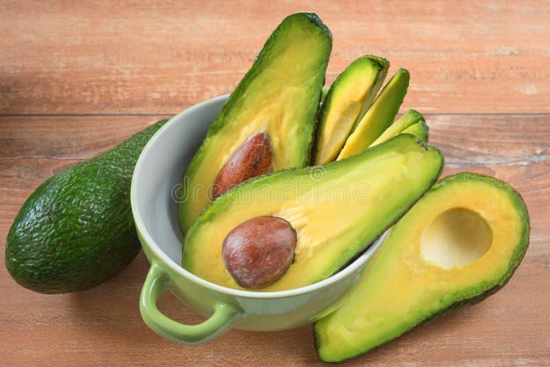 Foto del primo piano degli avocado affettati freschi, semi marroni visibili in ciotola verde su fondo di legno marrone immagine stock