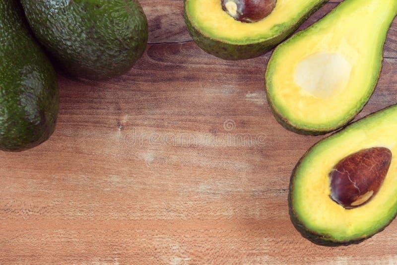 Foto del primo piano degli avocado affettati freschi, semi marroni visibili su fondo di legno marrone immagini stock libere da diritti