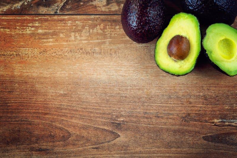 Foto del primo piano degli avocado affettati freschi, semi marroni visibili su fondo di legno marrone immagine stock