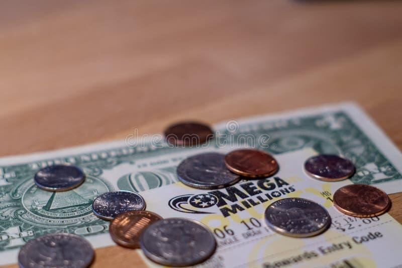 Foto del primo piano dei biglietti di lotteria di Mega Millions con la banconota in dollari e le monete immagini stock libere da diritti