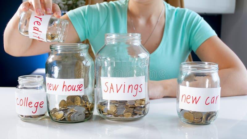 Foto del primo piano dei soldi di risparmio della giovane donna per comprare nuova casa fotografia stock