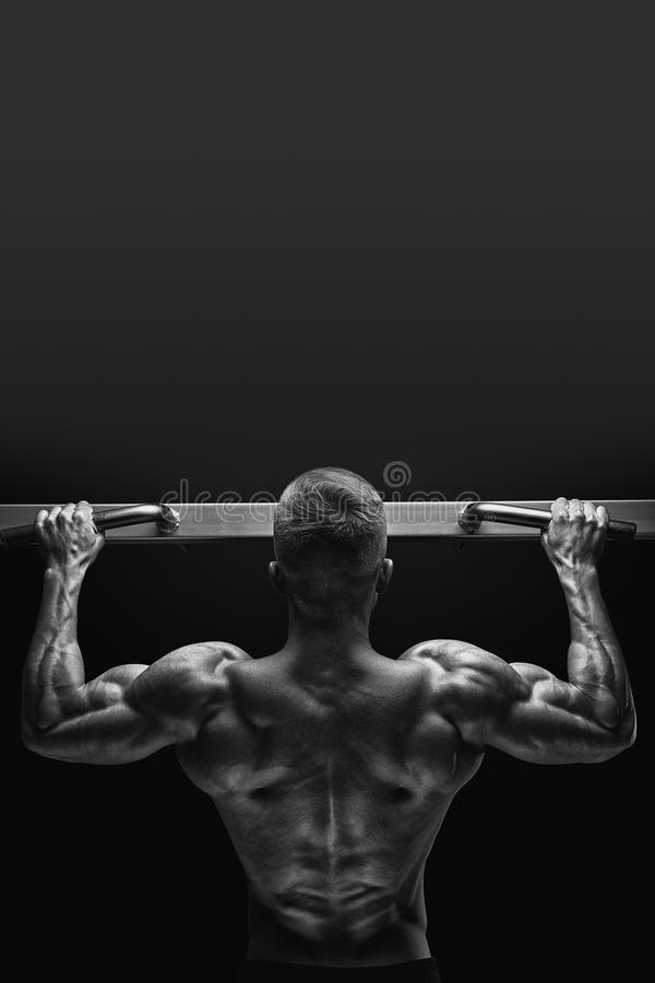 Foto del primo piano del tipo muscolare attraente del culturista che fa tirata fotografia stock libera da diritti