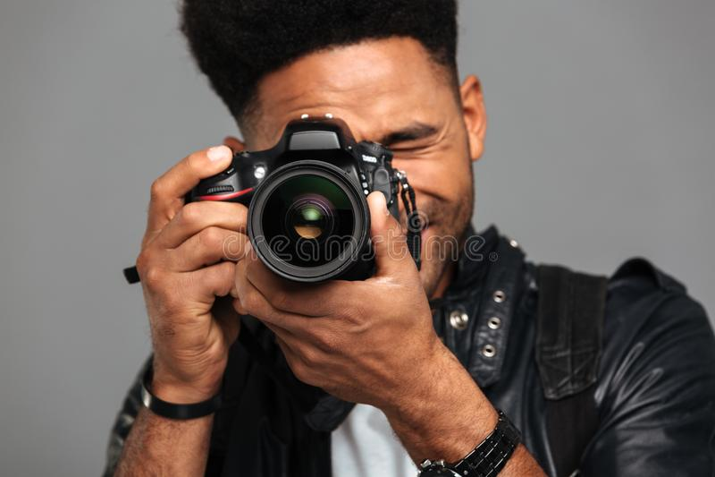 Foto del primo piano dell'uomo afroamericano concentrato che prende foto sopra immagini stock libere da diritti