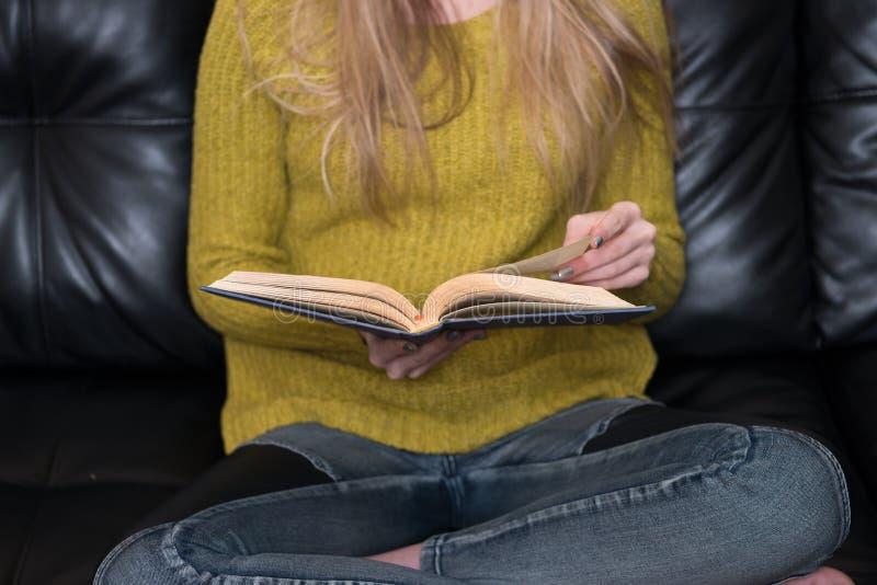 Foto del primo piano della donna che giudica vecchio libro seduta disponibila e leggente sul sofà a casa immagine stock