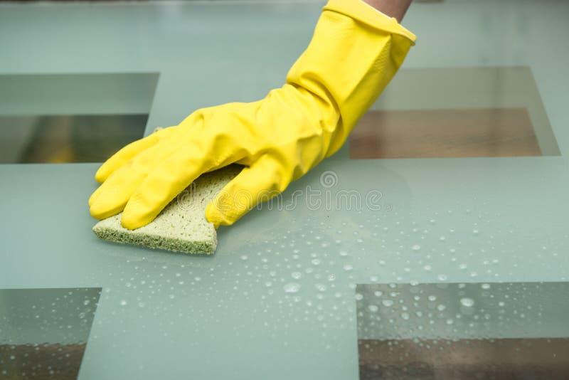 Foto del primo piano della mano femminile che lava tavola di vetro dentro con lo spruzzo di pulizia ed i guanti d'uso della spugn immagine stock