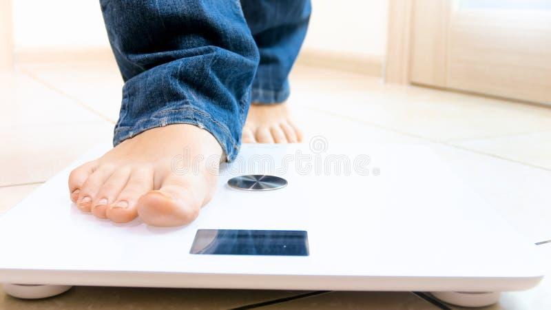 Foto del primo piano della persona scalza che fa un passo sulle scale elettroniche immagine stock libera da diritti