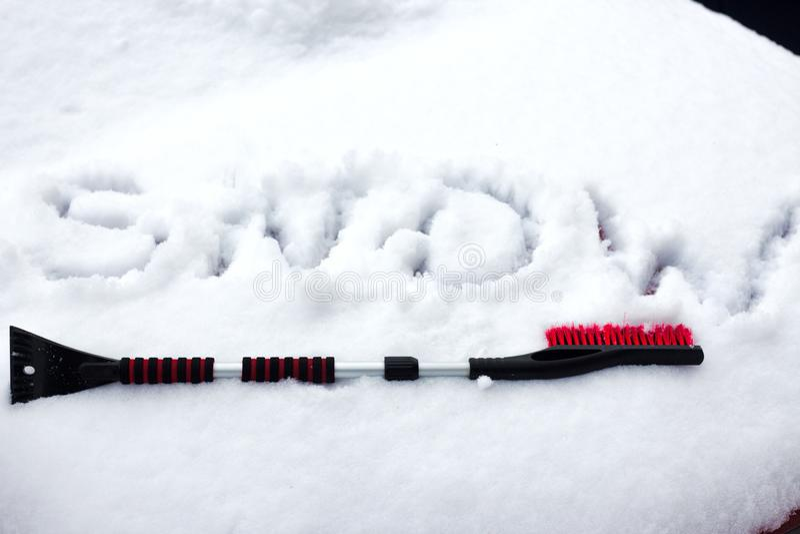 Foto del primo piano della spazzola nera che si trova sull'automobile coperta in neve fotografia stock libera da diritti