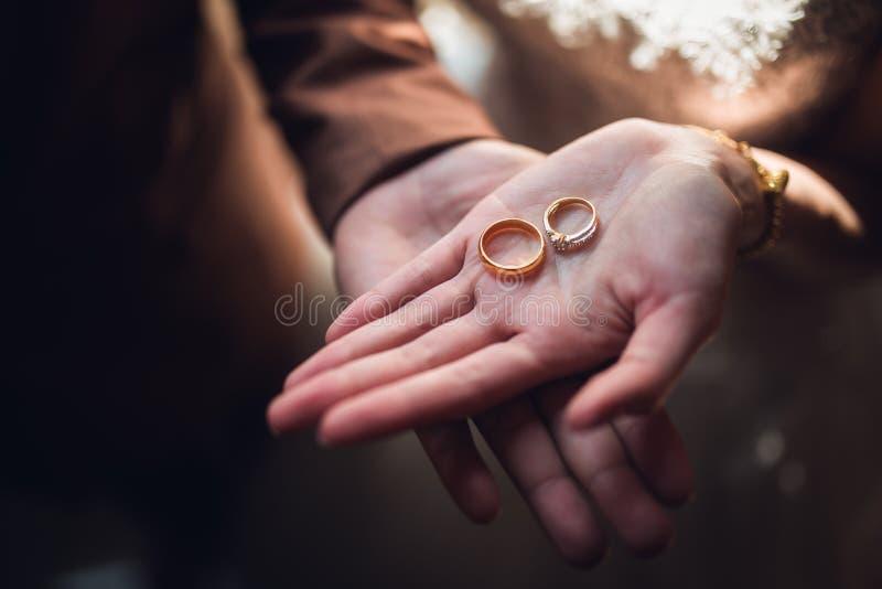 Foto del primo piano della sposa e dello sposo che tengono le fedi nuziali dorate sulle mani fotografia stock