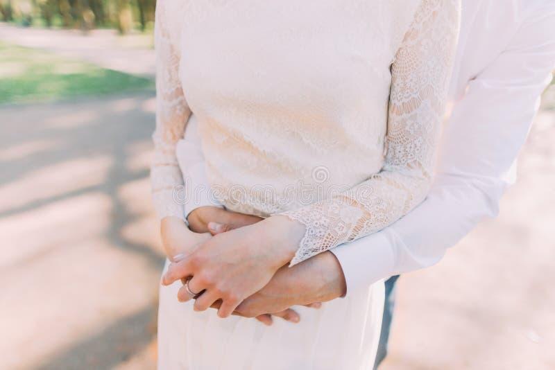 Foto del primo piano della sposa e dello sposo nell'abbraccio che si tengono per mano sul suo stomaco fotografia stock libera da diritti