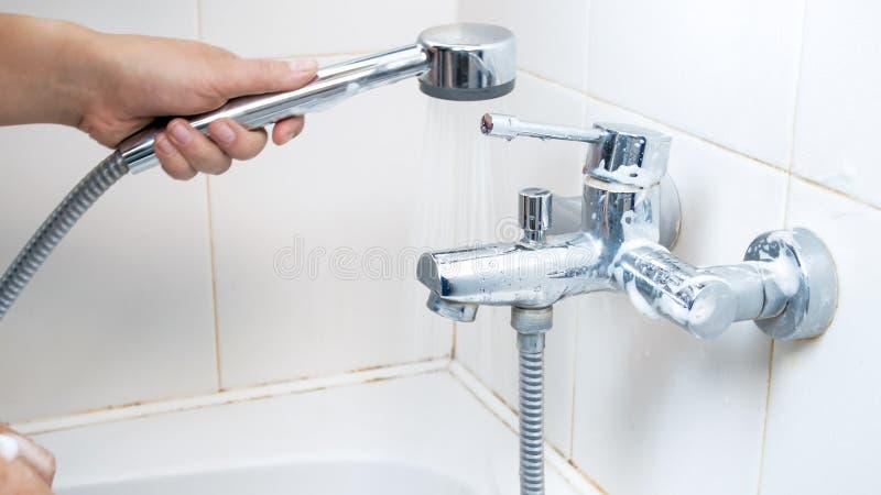 Foto del primo piano della testa di doccia femminile della tenuta della mano fotografie stock