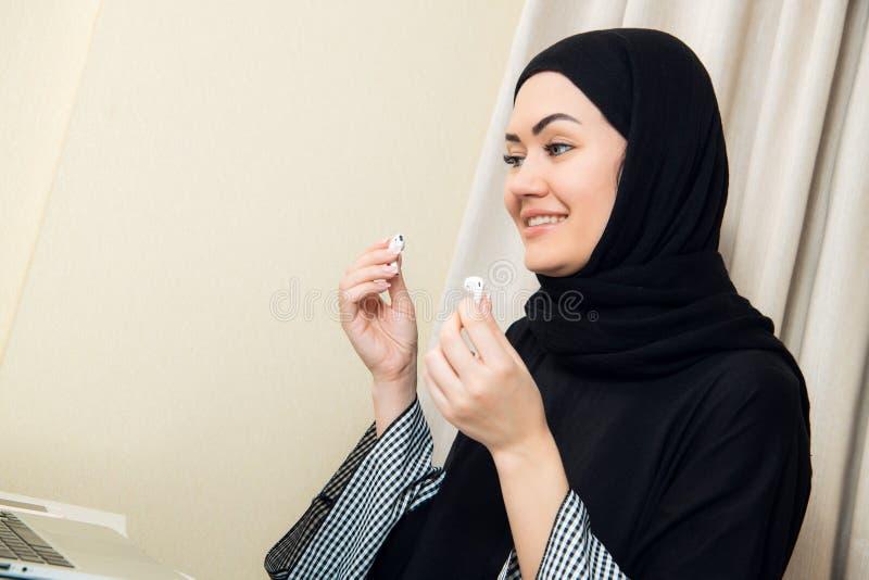 Foto del primo piano delle donne del hijab che ascoltano la musica facendo uso dei telefoni senza fili moderni dell'orecchio che  fotografia stock libera da diritti