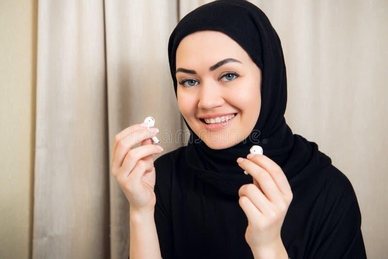 Foto del primo piano delle donne del hijab che ascoltano la musica facendo uso dei telefoni senza fili moderni dell'orecchio che  fotografie stock