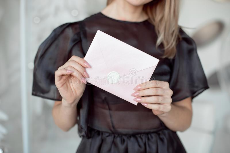 Foto del primo piano delle mani femminili che tengono una busta rosa dell'invito con una guarnizione della cera, un buono regalo, fotografia stock