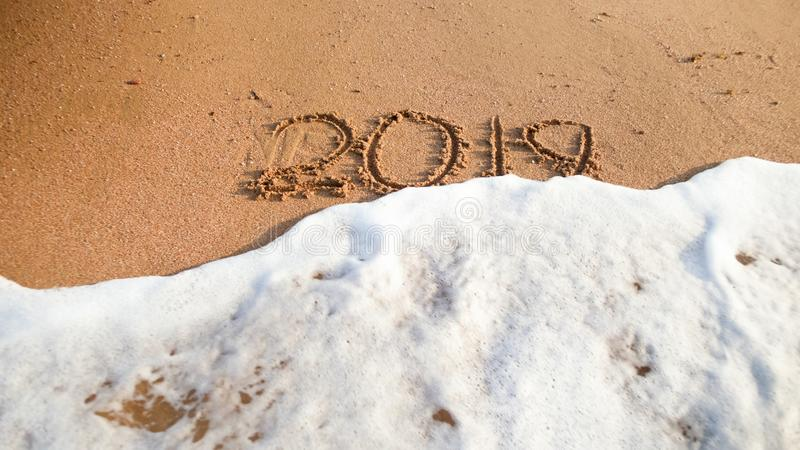 Foto del primo piano delle onde del mare che si rivoltano 2019 numeri scritti sulla sabbia bagnata alla spiaggia Concetto del nuo fotografia stock libera da diritti