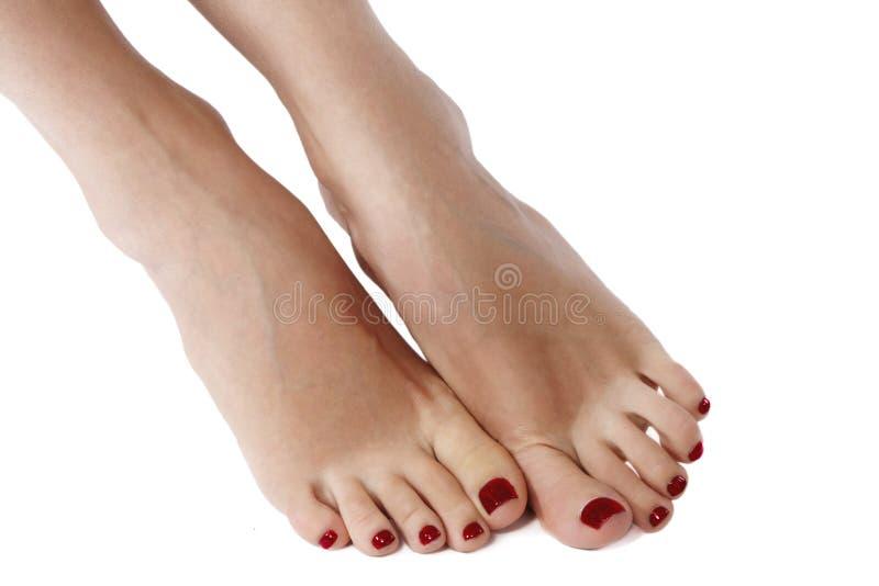 Foto del primo piano di bei piedi femminili con il pedicure rosso Pulisca la pelle molle, le unghie sane con la lucidatura del ge immagini stock libere da diritti