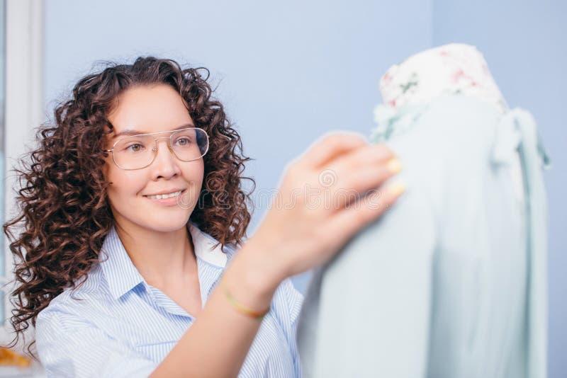 Foto del primo piano di giovane cucitrice che sta accanto al vestito sul manichino fotografie stock