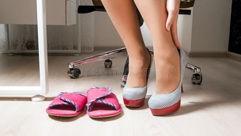 Foto del primo piano di giovane donna di affari che massaggia le gambe stanche e che cambia le scarpe fotografia stock