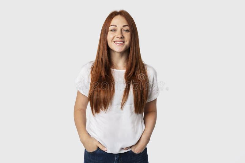 Foto del primo piano di giovane femmina europea emozionale isolata su fondo grigio Ragazza dai capelli rossi in una maglietta bia immagine stock