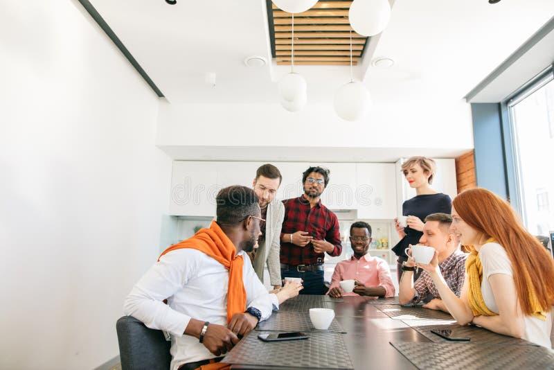 Foto del primo piano di giovane gruppo di affari che ha conversazione dentro fotografie stock