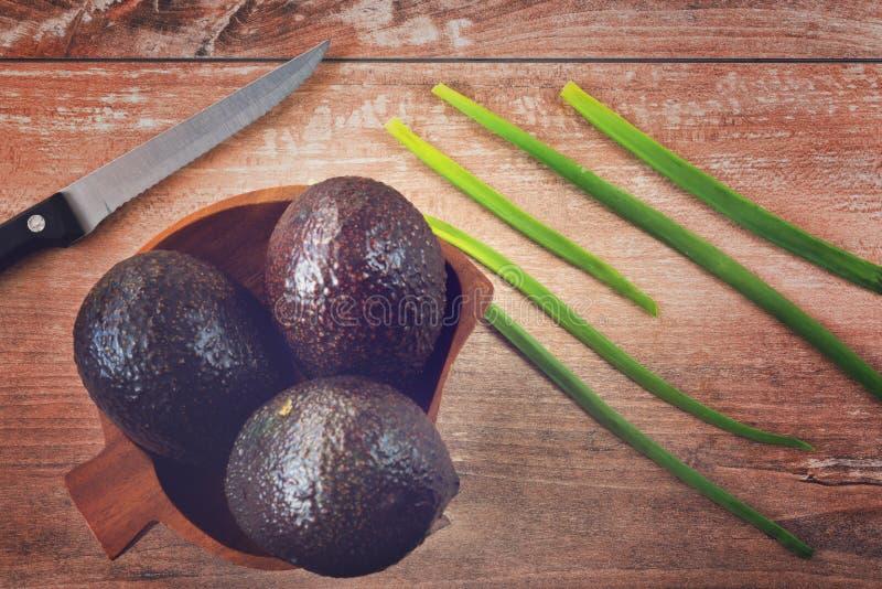 Foto del primo piano di interi avocado freschi e della cipolla fresca in ciotola di legno marrone su fondo di legno marrone fotografia stock libera da diritti