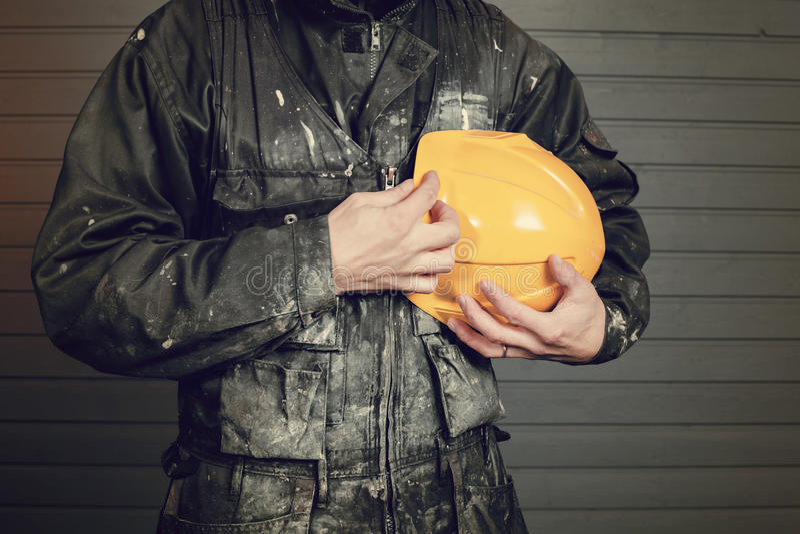 Foto del primo piano di laborer& sporco x27; camici di s e un casco di sicurezza giallo immagine stock