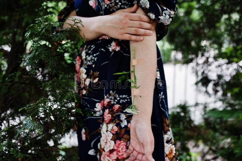 Foto del primo piano di un fiore legato ad un braccio femminile fotografia stock