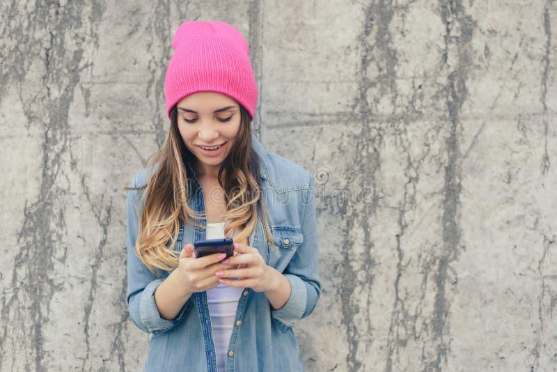 Foto del primo piano del testo sorridente della lettura della ragazza dei pantaloni a vita bassa sullo smartphone È molto felice  fotografia stock