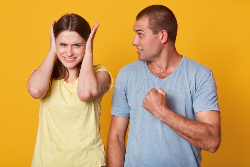 Foto del puño enojado peligroso de la tenencia del hombre, yendo a hacer el dolor para su novia, mirándola con el descontento, ne fotografía de archivo libre de regalías