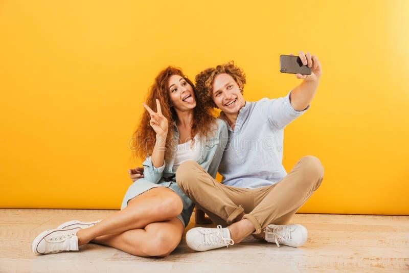 Foto del ragazzo allegro e dell'amica 20s che si siedono sul pavimento fotografia stock