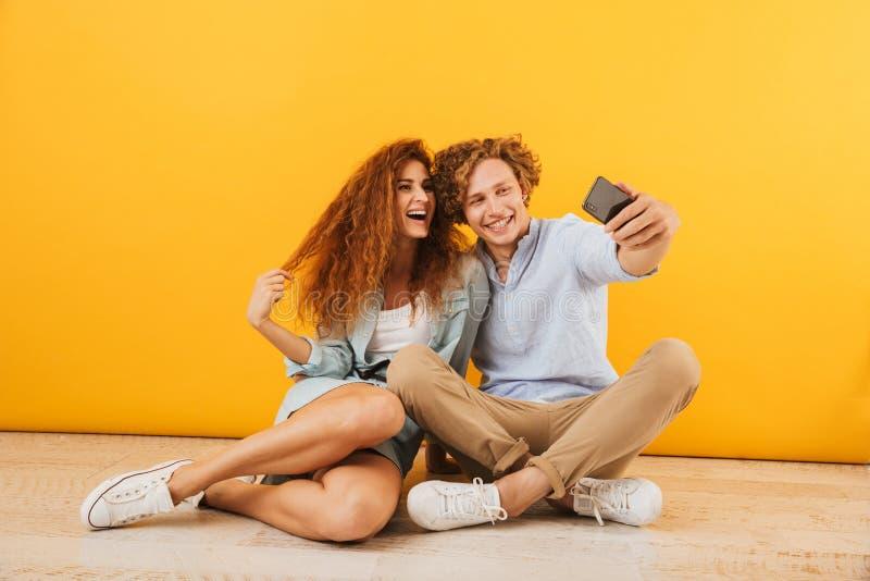 Foto del ragazzo gioioso e dell'amica 20s che si siedono sul pavimento a immagini stock