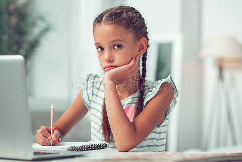 Foto del ritratto del primo piano di piccolo scolaro adorabile afroamericano che fa compito fotografie stock