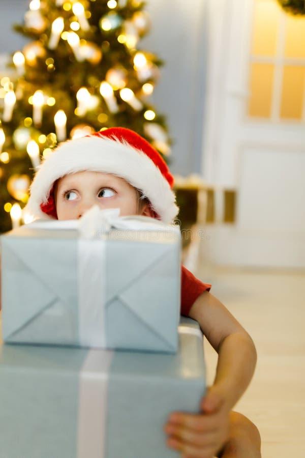 Foto del ` s del nuovo anno del ragazzo in cappuccio del ` s di Santa con il contenitore di regalo su fondo fotografia stock