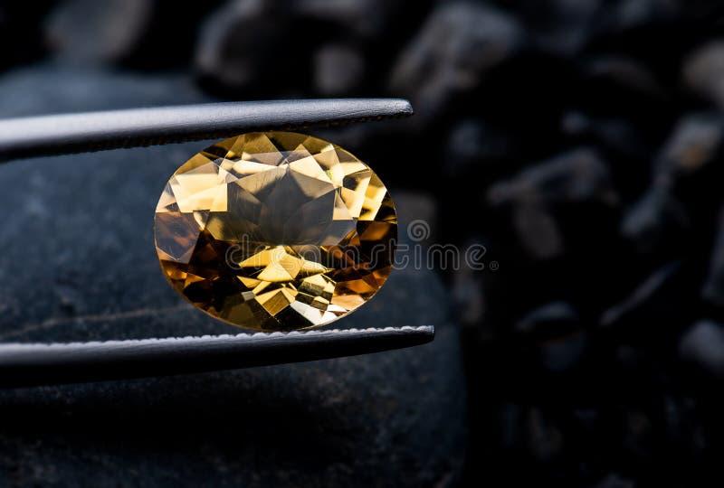 Foto del taglio dei gioielli della pietra preziosa del quarzo fumoso con fondo d'accensione scuro fotografia stock libera da diritti