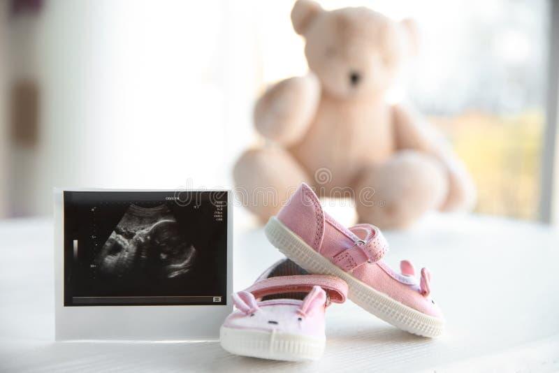 Foto del ultrasonido del bebé y de botas lindas en la tabla fotos de archivo