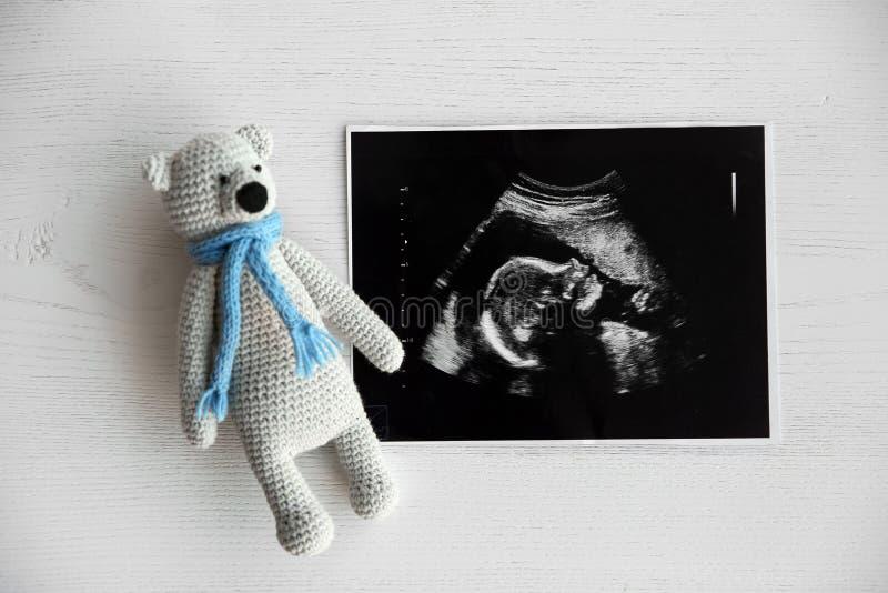 Foto del ultrasonido del bebé y juguete en fondo de madera fotos de archivo