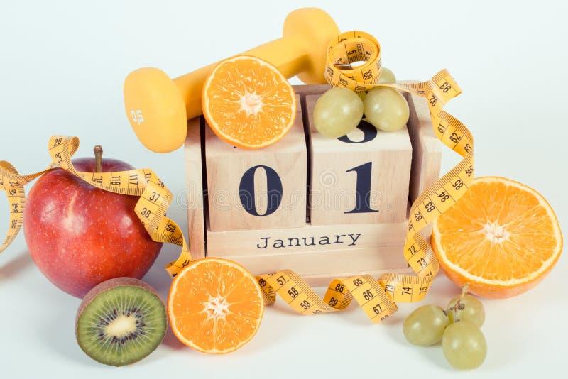 Foto del vintage, calendario del cubo, frutas, pesas de gimnasia y cinta métrica, Años Nuevos de resoluciones foto de archivo