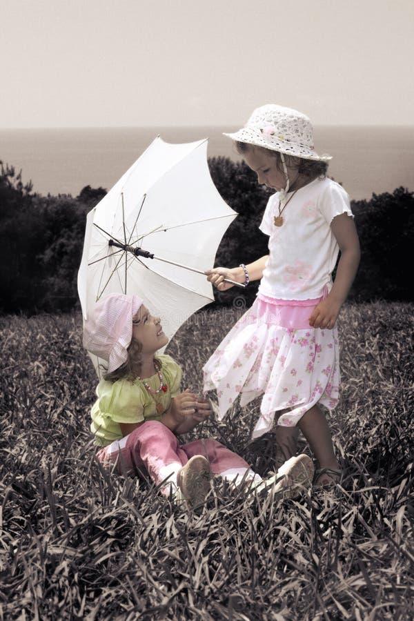 Foto del vintage con las muchachas con el paraguas en césped imagen de archivo libre de regalías