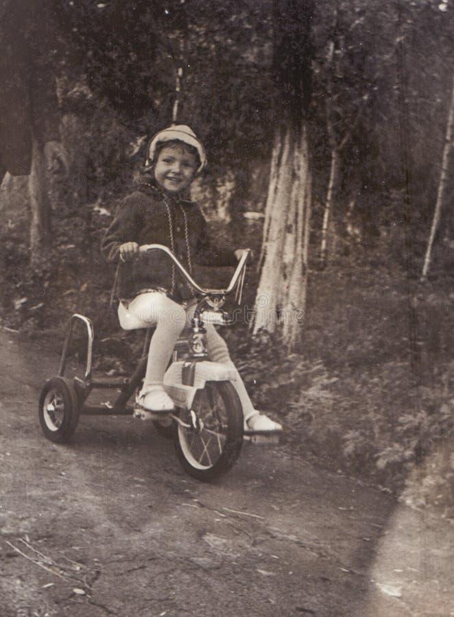 Foto del vintage de la niña en la bicicleta vieja foto de archivo