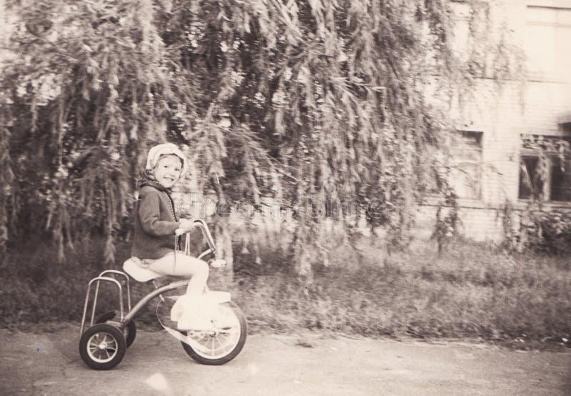 Foto del vintage de la niña en la bicicleta vieja imagen de archivo libre de regalías
