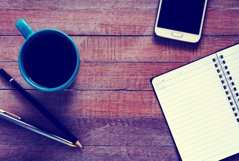 Foto del vintage de la opinión superior sobre el cuaderno, el smartphone, la pluma y la taza de café abiertos foto de archivo libre de regalías