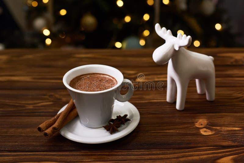 Foto del vintage, especias, café caliente en la taza blanca y árbol de navidad con las luces en fondo fotos de archivo libres de regalías