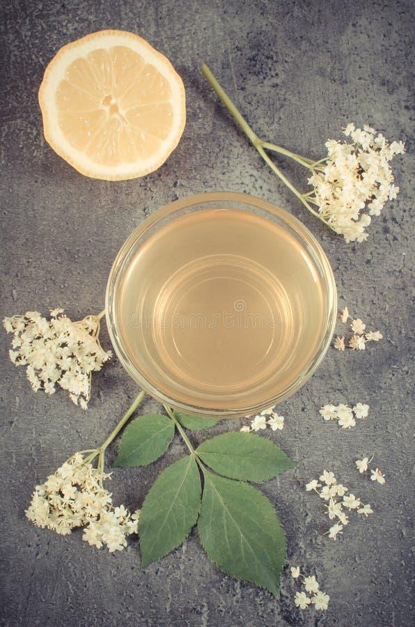 Foto del vintage, jugo sano fresco, flores de la baya del saúco y limón en la estructura del hormigón imágenes de archivo libres de regalías