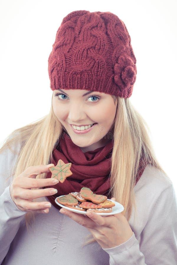 Foto del vintage, mujer sonriente en casquillo de lana y mantón que sostiene los panes de jengibre, tiempo de la Navidad imágenes de archivo libres de regalías