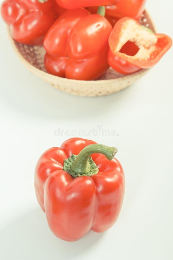 Foto del vintage, pimientas maduras rojas con la cesta de mimbre en el fondo blanco, nutrición sana imágenes de archivo libres de regalías