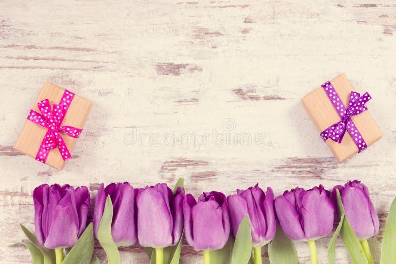 Foto del vintage, ramo de tulipanes púrpuras y regalos para diversas ocasiones en los tableros blancos fotografía de archivo