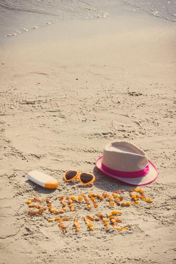 Foto del vintage, tiempo de verano de la inscripción, gafas de sol, loción del sol y sombrero de paja en la arena en la playa, ti fotos de archivo libres de regalías